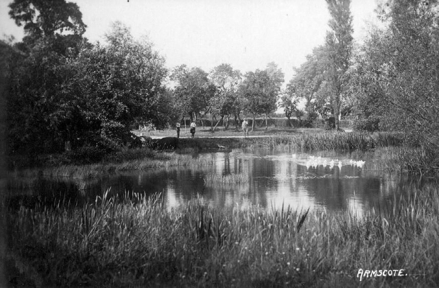 A pond backed by an orchard at which three men are fishing, Armscote.  1920s |  IMAGE LOCATION: (Warwickshire County Record Office)