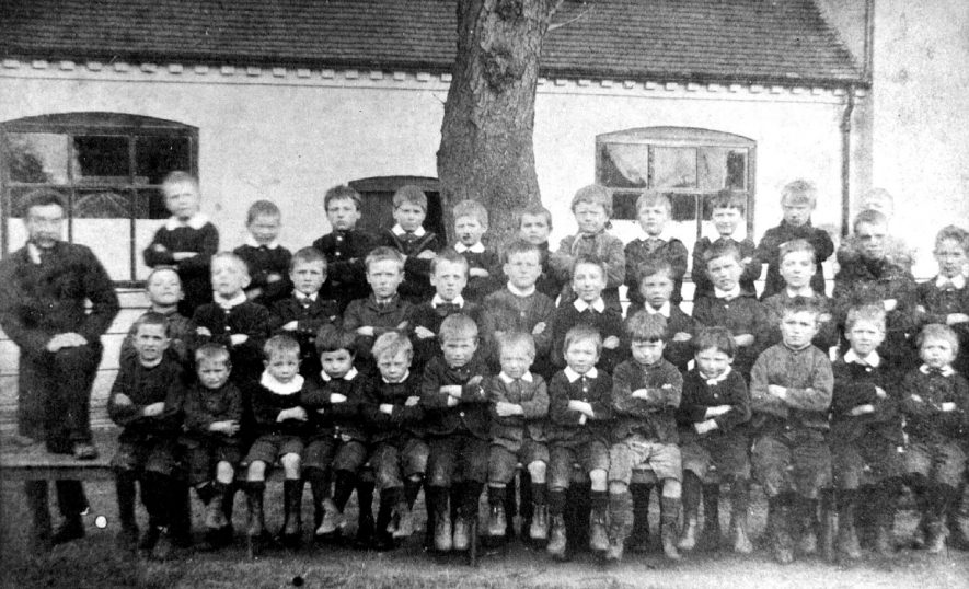 Nether Whitacre school group in 1885. On the back row 3rd and 5th from left are the Parlett brothers and 1st and 2nd from right are John and William Collins. |  IMAGE LOCATION: (Warwickshire County Record Office) PEOPLE IN PHOTO: Parlett as a surname, Collins, William, Collins, John, Collins as a surname
