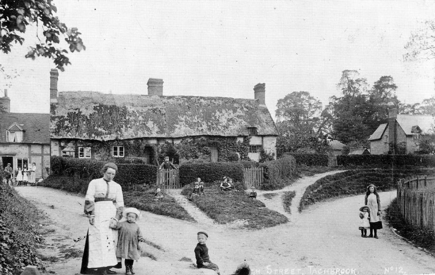 An old thatched cottage with people around, Bishops Tachbrook.  1900s