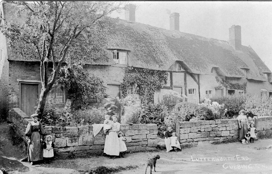 Women, children and pets standing in front of thatched and timbered cottages in Lutterworth End (now Church Lane), Cubbington.  1900s For more detailed information refer to - Cubbington by G.F.Peppitt. |  IMAGE LOCATION: (Warwickshire County Record Office)
