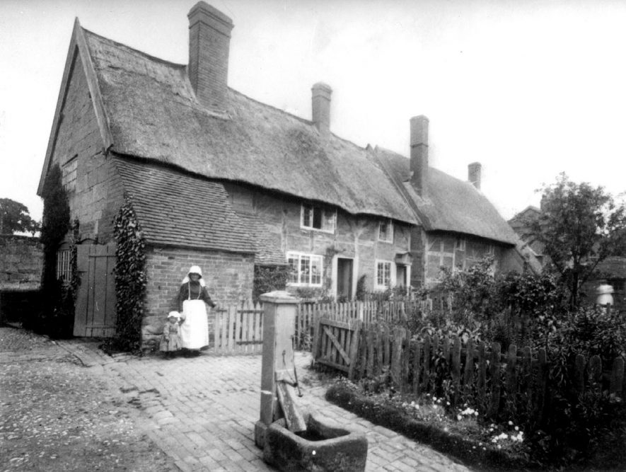 Thatched and timbered cottages at the lower end of Queen Street, Cubbington. In the foreground is a water pump above a well which would have served several cottages.  Standing behind is Mrs Wells and child.  1900s  For more detailed information refer to - Cubbington by G.F.Peppitt. |  IMAGE LOCATION: (Warwickshire County Record Office) PEOPLE IN PHOTO: Wells, Mrs