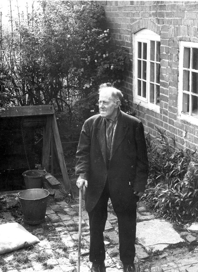 Cottage (now demolished) in Cross Lane, Cubbington. Note the draw well behind the man in the picture.  1950s For more detailed information refer to - Cubbington by G.F.Peppitt. [The man in the oicture is Mr Tearne] |  IMAGE LOCATION: (Warwickshire County Record Office)