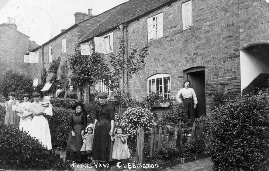 Back to back houses with cellars in Penns Yard ( now Penns Close). Group of women and children standing in front of the small front gardens. Standing by the door are Mrs Stanley and Mrs Kenzitt. On the pathway are Emily Stanley, Mrs Goode, Mrs Skelsey, Miss Barber, Sara Butler, Mrs Beesley and unnamed child.  1900s