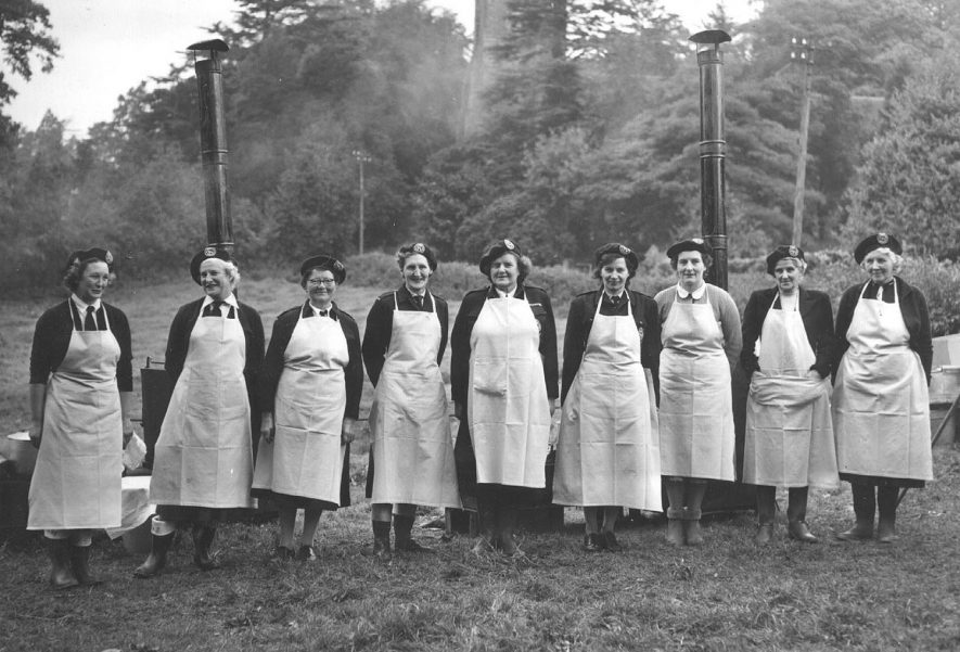 Emergency feeding exercise by Civil Defence Corps ( Welfare Section ) showing volunteers, from left to right, Mrs M. Mayall, Mrs. K. Wyatt, Miss M. Waters, Mrs. M. Kynaston, Miss J. de Trafford, Section Leader Mrs. E. Herbert, Mrs. L. Kempley, Mrs. A. Worrall, and Mrs M. Sumner.  Avon Dassett.  1957 |  IMAGE LOCATION: (Warwickshire County Record Office) PEOPLE IN PHOTO: Worrall, Mrs A, Worrall as a surname, Waters, Miss M, Waters as a surname, Trafford, Miss J de, Trafford, de as a surname, Sumner, Mrs M, Sumner as a surname, Mayall, Mrs M, Mayall as a surname, Kynaston, Mrs M, Kynaston as a surname, Kempley, Mrs L, Kempley as a surname, Herbert, Mrs E, Herbert as a surname