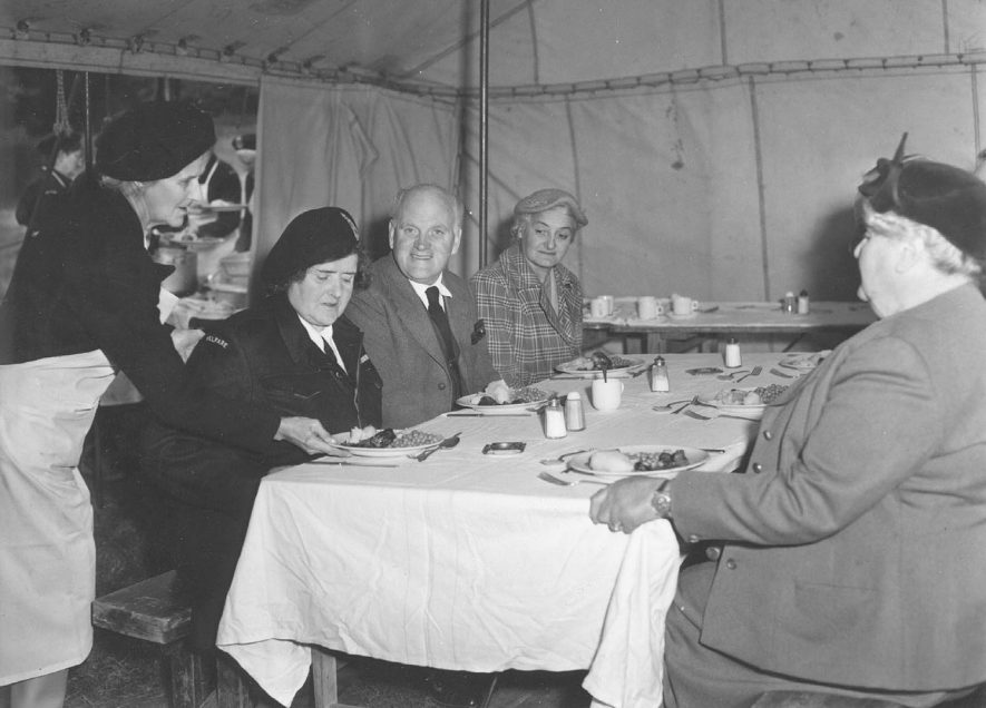 Emergency Feeding Exercise showing Mrs M. Sumner serving lunch in Food Preparation Tent to (left to right) Miss J. de Trafford, Section Leader, Mr J. Richmond, Civil Defence Officer, Southam, Mrs A. Howlett and Lady Victoria de Trafford. Avon Dassett.  1957 |  IMAGE LOCATION: (Warwickshire County Record Office) PEOPLE IN PHOTO: Trafford, Miss J de, Trafford, Lady Victoria de, Trafford, de as a surname, Sumner, Mrs M, Sumner as a surname, Richmond, Mr J, Richmond as a surname, Howlett, Mrs A, Howlett as a surname