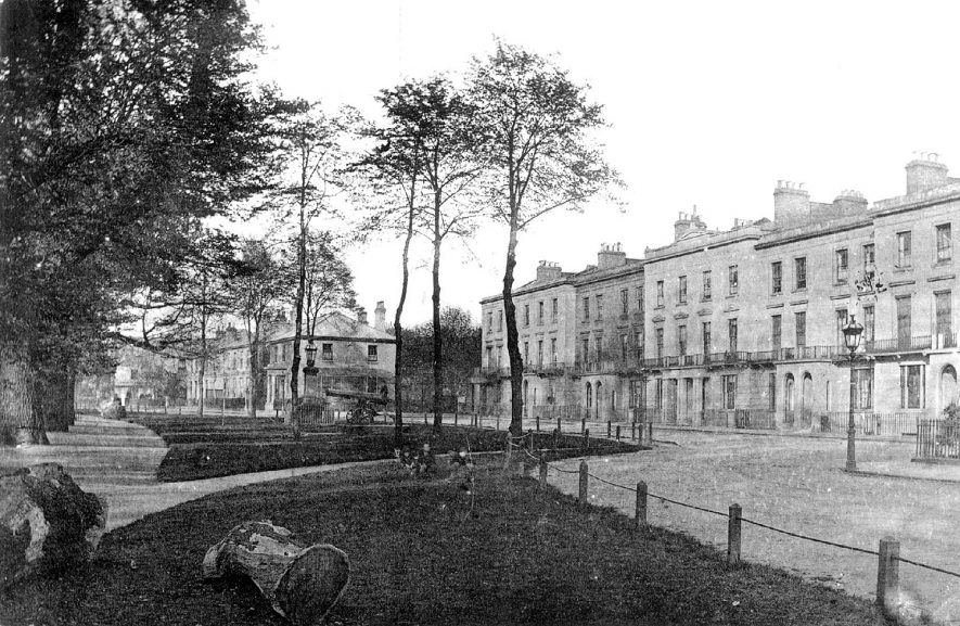 Large town houses and tree lined walk with cannon and gun carriage in the background. Holly Walk, Leamington Spa.  1900s |  IMAGE LOCATION: (Warwickshire Museums. Photographic Collections.)
