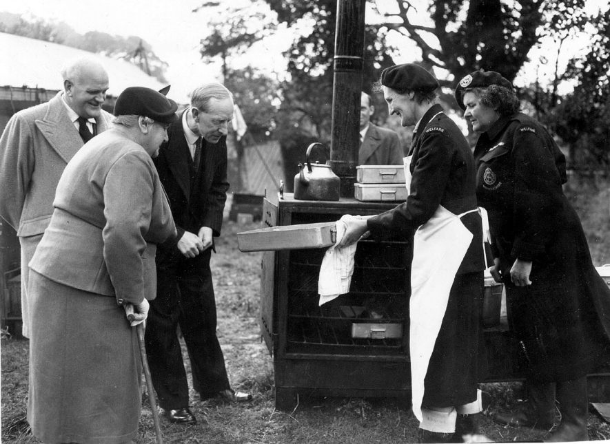 Avon Dassett, emergency  feeding exercise showing Mrs M. Kynaston showing the Yorkshire Pudding baked in the oven of No 4 Field Cooker to, left to right, Mr. J. Richmond, Civil Defence Officer, Southam, Lady Victoria de Traford and Mr A.R. Browne, Assistant Director of Education and Emergency Meals Officer, Warwickshire.  Right is Miss J. de Trafford, Section Leader.  1957 |  IMAGE LOCATION: (Warwickshire County Record Office) PEOPLE IN PHOTO: Trafford, Miss J de, Trafford, Lady Victoria de, Trafford, de as a surname, Richmond, Mr J, Richmond as a surname, Kynaston, Mrs M, Kynaston as a surname, Browne, Mr A R, Browne as a surname
