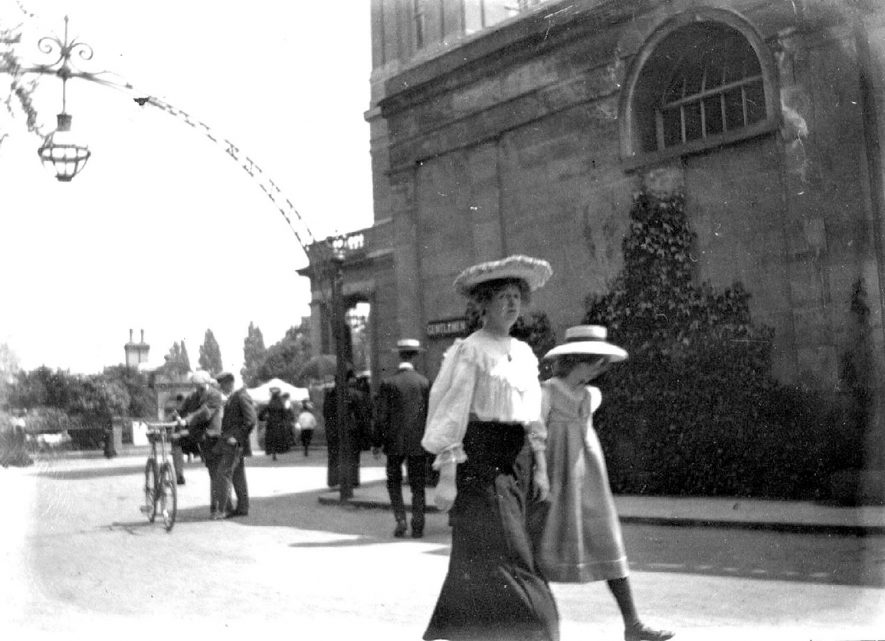 Leamington Spa.  Gardens outside the Pump Rooms.  Lady and young girl walking, men and bicycle in distance.  1900s |  IMAGE LOCATION: (Warwickshire Museums. Photographic Collections.)