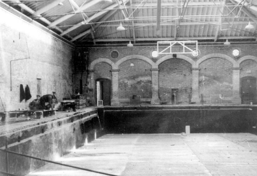Leamington Spa Pump Rooms swimming bath, empty and with workmen on side.  1900s |  IMAGE LOCATION: (Warwickshire Museums. Photographic Collections.)