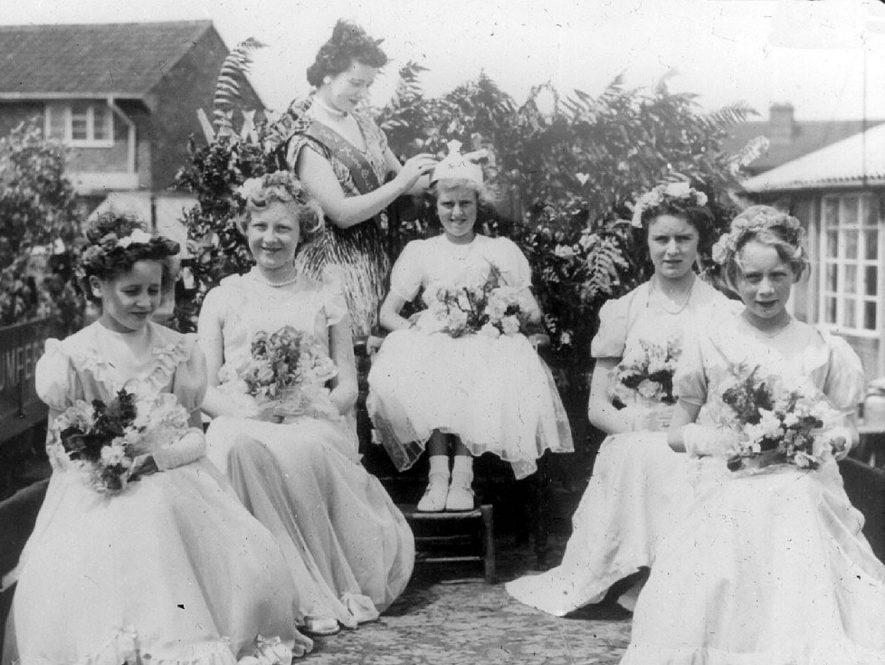 Crowning of the Carnival Queen, Cubbington. Left to right - Josie Fleming, Moira Timms, Marjorie Middleton crowning Joyce Lambert, Wendy Morris and Pat Ovard.  1960s |  IMAGE LOCATION: (Warwickshire County Record Office) PEOPLE IN PHOTO: Ovard, Pat, Morris, Wendy, Middleton, Marjorie, Lambert, Joyce, Fleming, Josie