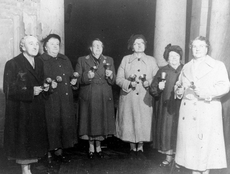 Handbell ringers of the Darby & Joan Club in Cubbington. From left to right - Mrs Mullis, Annie Draper, Mrs Skelsey, Mrs Carpenter, Mrs Stanley, Mrs Fox.  1950s |  IMAGE LOCATION: (Warwickshire County Record Office) PEOPLE IN PHOTO: Stanley, Mrs, Skelsey, Mrs, Mullis, Mrs, Fox, Mrs, Draper, Annie, Carpenter, Mrs