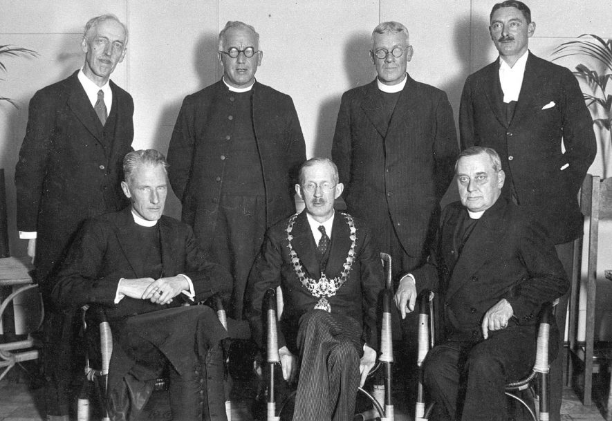 The induction of the Reverend G.C. Rolfe as vicar of All Saint's Church, Leamington Spa.  October 1933 Back row - Charles W. Jackson, churchwarden, Revd. St Barbe Holland, Archdeacon of Warwick, Revd. Mostyn Robinson, Rural Dean and vicar of St Mark's, Gerald C.W.Large, registrar. Front row - The Rt. Revd. Mervyn Haigh, The Bishop of Coventry, Cllr.. Edmund Jones, Mayor of Leamington, Revd. G.C. Rolfe, vicar. |  IMAGE LOCATION: (Warwickshire County Record Office) PEOPLE IN PHOTO: Rolfe, Revd G C, Robinson, Revd Mostyn, Large, Gerald C W, Jones, Edmund, Jackson, Charles W, Holland, Revd St Barbe, Haigh, Rt Revd Mervyn