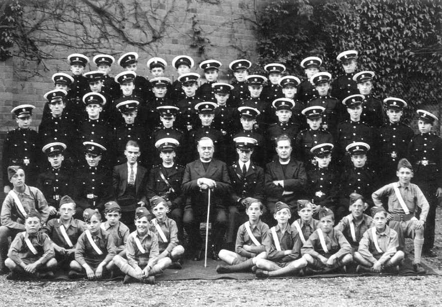 All Saint's Church Lads Brigade in the vicarage gardens in 1936. Captain - Revd. Cyril Walters and the vicar - Revd. G.C. Rolfe. Leamington Spa.    IMAGE LOCATION: (Warwickshire County Record Office) PEOPLE IN PHOTO: Walters, Revd Cyril, Rolfe, Revd G C