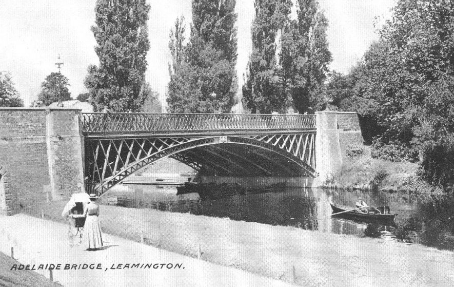 Adelaide Bridge over the River Leam, Leamington Spa. Woman pushing pram along the towpath and man rowing boat on the river.  1900s |  IMAGE LOCATION: (Warwickshire County Record Office)