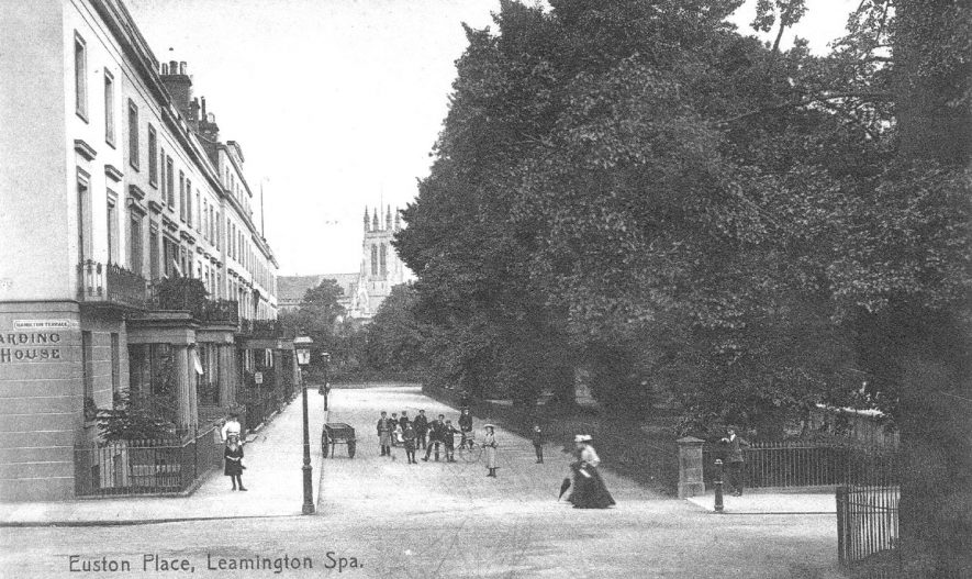 Euston Place, Leamington Spa.  Terraced houses, railed gardens, children in street, handcart.  Parish church tower.  1900s |  IMAGE LOCATION: (Warwickshire County Record Office)