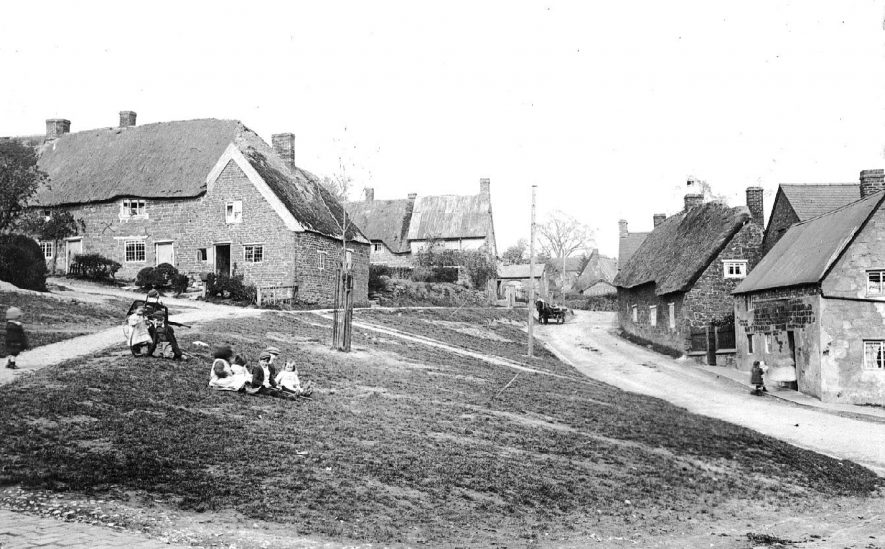A Napton street showing cottages.  Village children including one with a hoop and one with a hand/dog cart.  Horse and cart in background.  c.1905 |  IMAGE LOCATION: (Warwickshire County Record Office) IMAGE DATE: (c.1905)