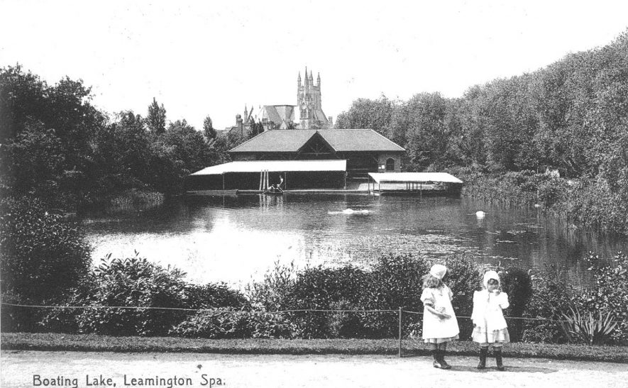 Boating lake with boathouse and parish church spire in distance, Leamington Spa. Two small girls on path.  1900s  |  IMAGE LOCATION: (Warwickshire County Record Office)