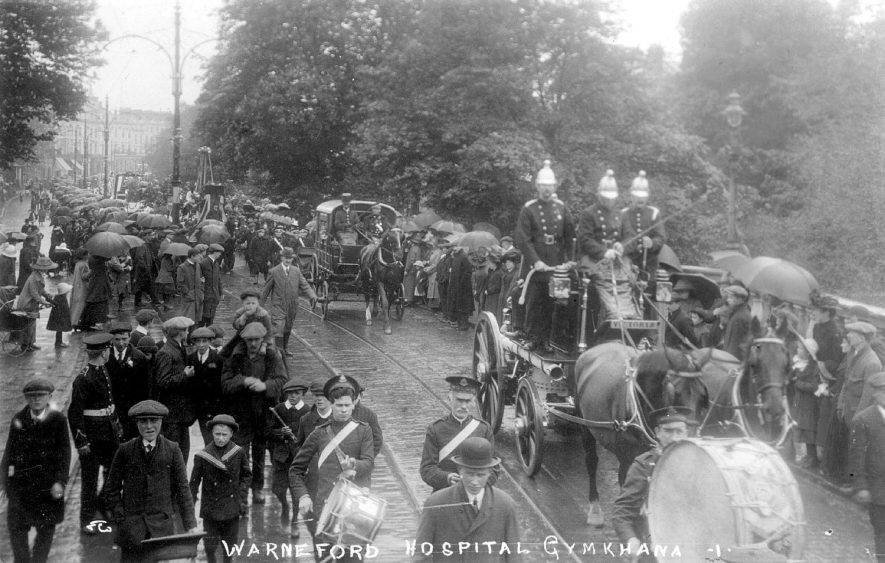 Warneford Hospital gymkhana parade with horse drawn fire engine, a band and other floats passing over Victoria Bridge, Leamington Spa.  1910s |  IMAGE LOCATION: (Warwickshire County Record Office)