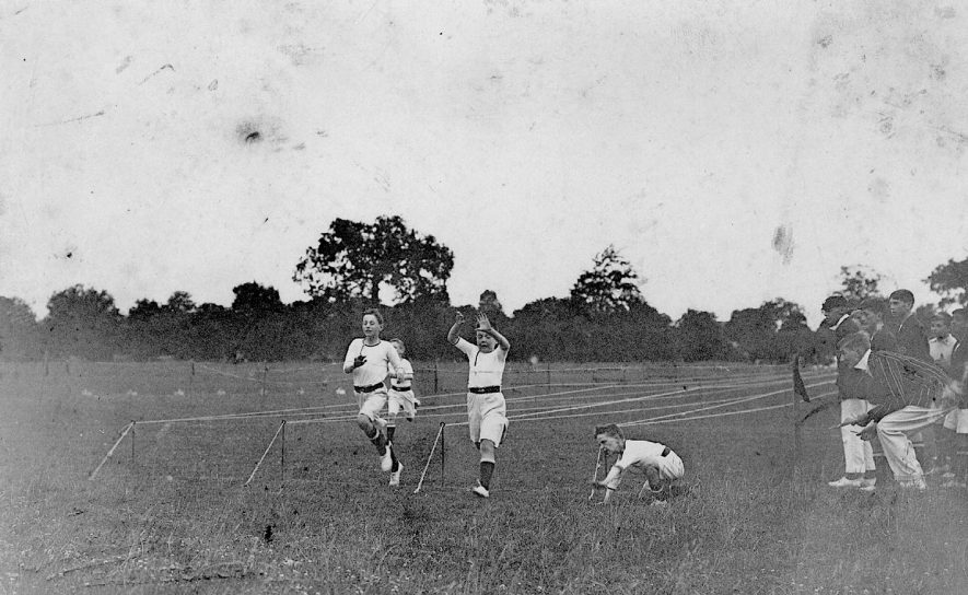 Boy's 100 yards sprint race, Leamington Spa.   Winner T. Hill.   Left to right:  Reynolds, Chalmers, Chernsides(?) T. Hill, Mr Shipman holding tape, P. Brookland, L. Kennan, Howden, C. Wells, Reed.  1920s |  IMAGE LOCATION: (Warwickshire County Record Office)