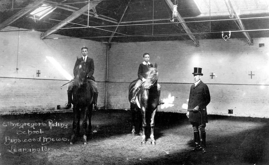 Macgreger's Riding School, Binswood Mews, Leamington Spa.  Interior of building, showing two schoolboys on horseback and instructor.  1900s |  IMAGE LOCATION: (Warwickshire County Record Office)