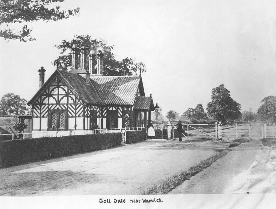 Toll gate near Warwick on Stratford Road with two people standing outside the building.  1910s [It has been suggested turnpike's powers expired in 1872, so would have a gate after that date, also the dress was not of this period. The house was removed to Barford, date not known.] |  IMAGE LOCATION: (Warwickshire County Record Office)