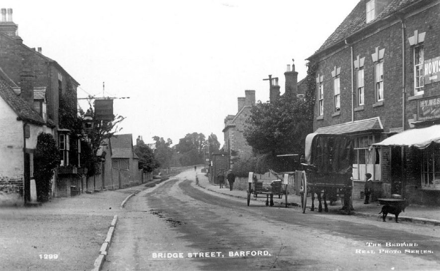 Bridge Street, Barford, with houses, shop and inn. Horse-drawn vehicles on roadside.  1910s |  IMAGE LOCATION: (Warwickshire County Record Office)