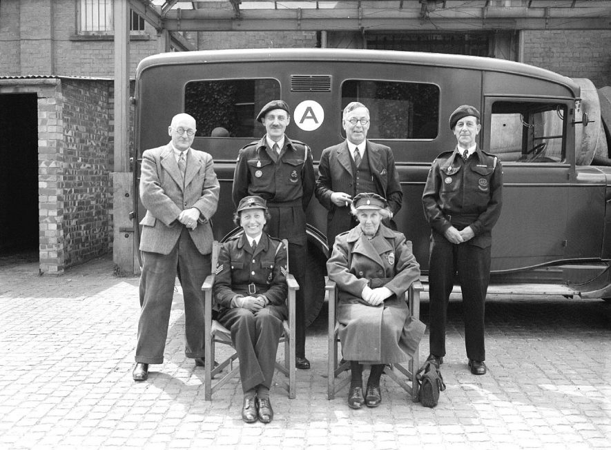 Gerald Clayton's ambulance group at central depot, Leamington Spa.  Ambulance in background.  29th May 1945 |  IMAGE LOCATION: (Warwickshire County Record Office) PEOPLE IN PHOTO: Clayton, Gerald