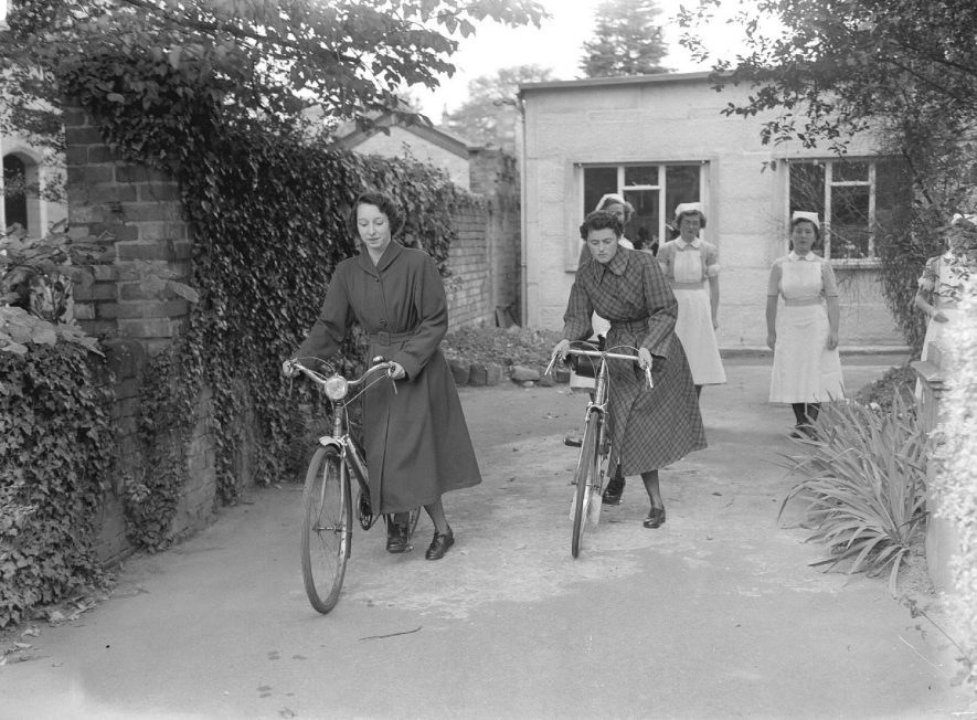Two nurses with bikes and other nurses in uniform at the Nurses' Home, St Mary's Road, Leamington Spa.  23rd September 1954 |  IMAGE LOCATION: (Warwickshire County Record Office)