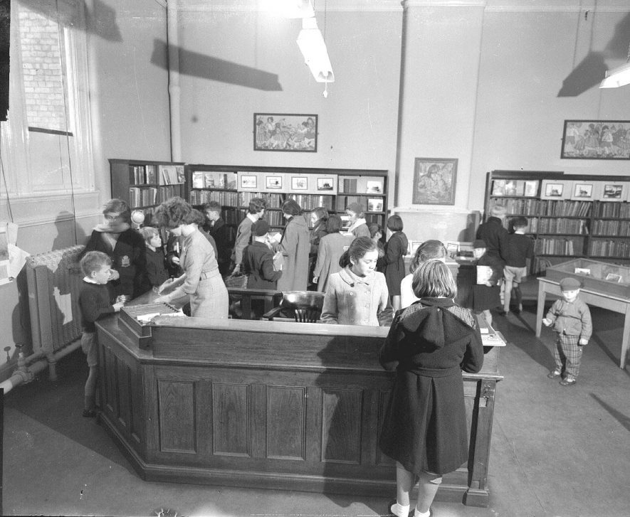 Leamington Spa Library interior, showing, desk, bookshelves, staff and public. 1960October 1960. |  IMAGE LOCATION: (Warwickshire County Record Office)