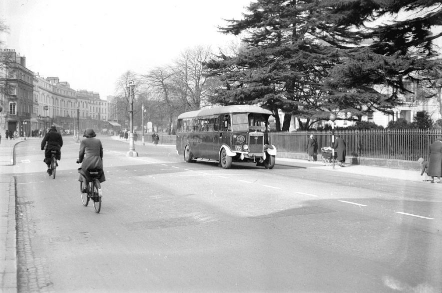 A Midland Red bus, passing Euston Place gardens, Leamington Spa,  before  the removal of the railings, for the war effort.  May 1940 |  IMAGE LOCATION: (Warwickshire County Record Office)