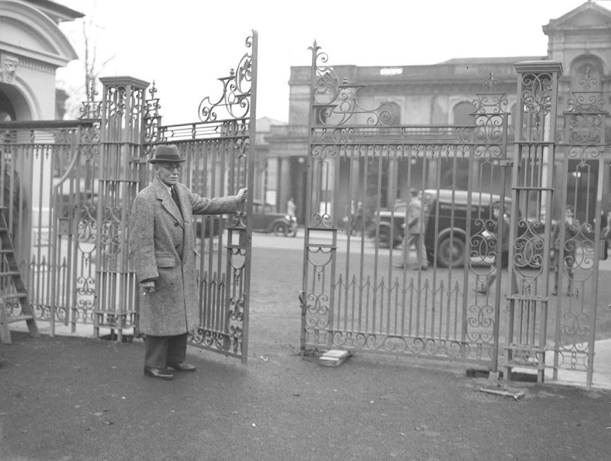 New gates at the entrance to Jephson Gardens, Leamington Spa, with the Pump Rooms in the background and an unknown man holding the gate open.  November 18th 1948 |  IMAGE LOCATION: (Warwickshire County Record Office)