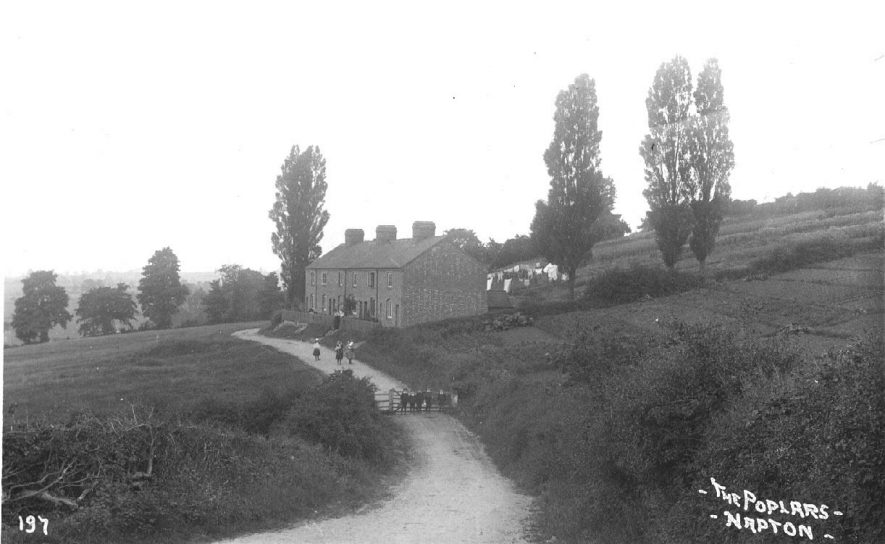 The Poplars - a line of terraced cottages amongst fields and allotments; children and some of the occupants are standing outside; washing on the line.  This road was originally called  Brickyards Lane.  c.1910   [Nos. 1-6 were 6 council houses, which leads to Brickyard Road. These were built by the former Southam Rural District Council.] |  IMAGE LOCATION: (Warwickshire County Record Office) IMAGE DATE: (c.1910)