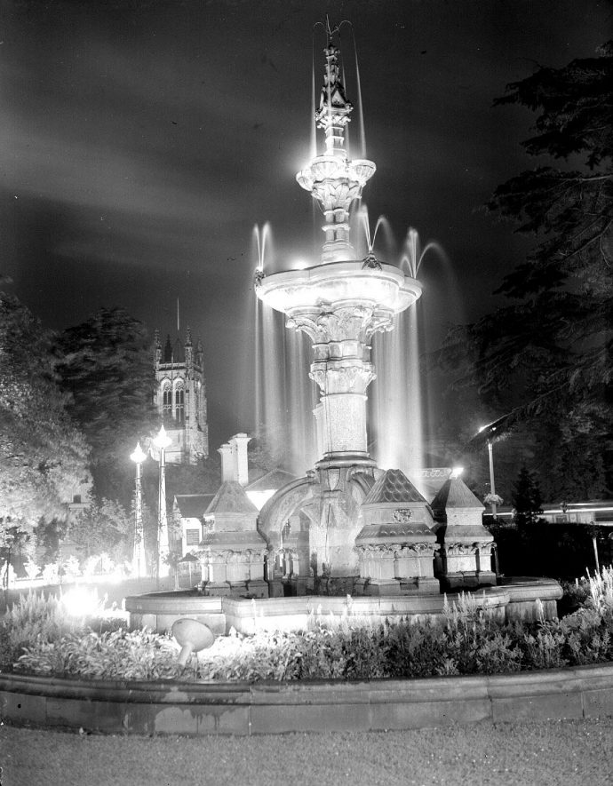 Hitchman Memorial Fountain, Jephson Gardens, Leamington Spa.  Parish Church tower in background.  Photograph from Leamington Lights series.  1953