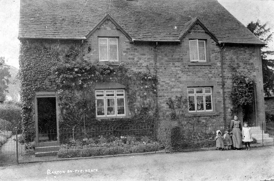 Barton on the Heath, showing two cottages with a group of a woman and three children outside one of them.  1900s |  IMAGE LOCATION: (Warwickshire County Record Office)