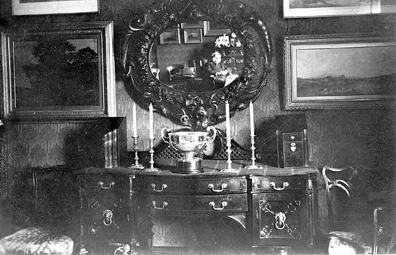 Interior of Baxterley rectory with a reflection of a clergyman in the mirror.  1900s |  IMAGE LOCATION: (Warwickshire County Record Office)