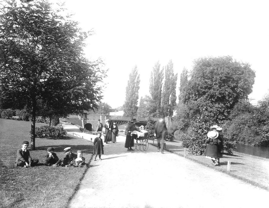 York Walk, looking toward Adelaide Bridge, with people in the park, children and perambulator, Leamington Spa.  1900s |  IMAGE LOCATION: (Warwickshire County Record Office)