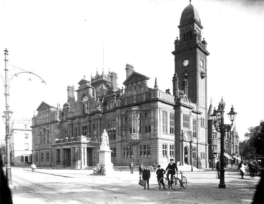 Town Hall, showing clock tower, part of Regent Grove and statue of Queen Victoria with boys with a bicycle, Leamington Spa.  1900s |  IMAGE LOCATION: (Warwickshire County Record Office)