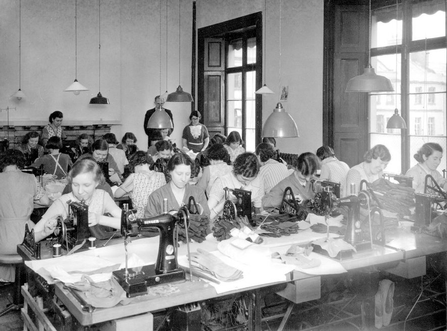 Sewing machinists making gloves in house, possibly at E.M. Ratcliffe and Co., 6, The Parade, Leamington Spa.  1930s |  IMAGE LOCATION: (Warwickshire County Record Office)
