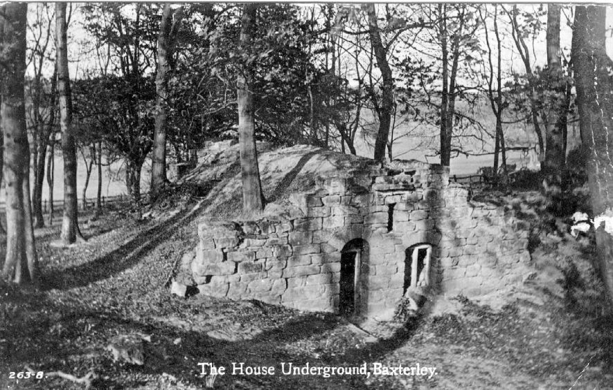 The House Underground, Baxterley. Stone frontage to house built into mound of earth. Trees growing on and around mound.  1920s |  IMAGE LOCATION: (Warwickshire County Record Office)