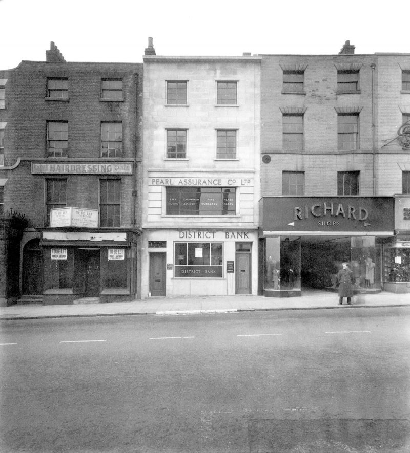 104-108 The Parade, Leamington Spa, showing front view of Richards Shops. District bank, Pearl Assurance Co. Ltd. and hairdresser's sign.  Soldier in street.  1940s |  IMAGE LOCATION: (Warwickshire County Record Office)
