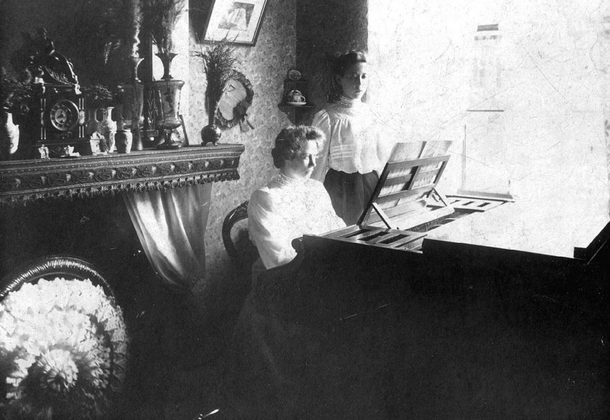 Two young ladies at a piano, one singing.  One is Miss Lilian Veal daughter of Eliza & Frederick Veal (photographer) taken at 45 Clapham Terrace, Leamington Spa.  1890s |  IMAGE LOCATION: (Warwickshire County Record Office) PEOPLE IN PHOTO: Veal, Lilian