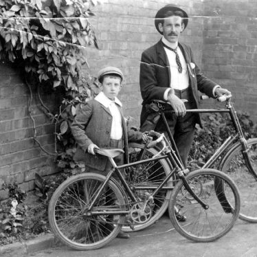 Leamington Spa.  A man and a boy with bicycles