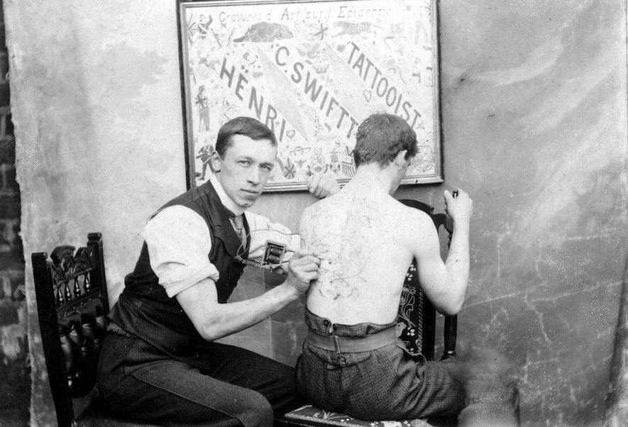 H C Swift, a tattooist at work in his premises at 22, Queen Street, Leamington Spa.  1900s |  IMAGE LOCATION: (Warwickshire County Record Office) PEOPLE IN PHOTO: Swift, H C