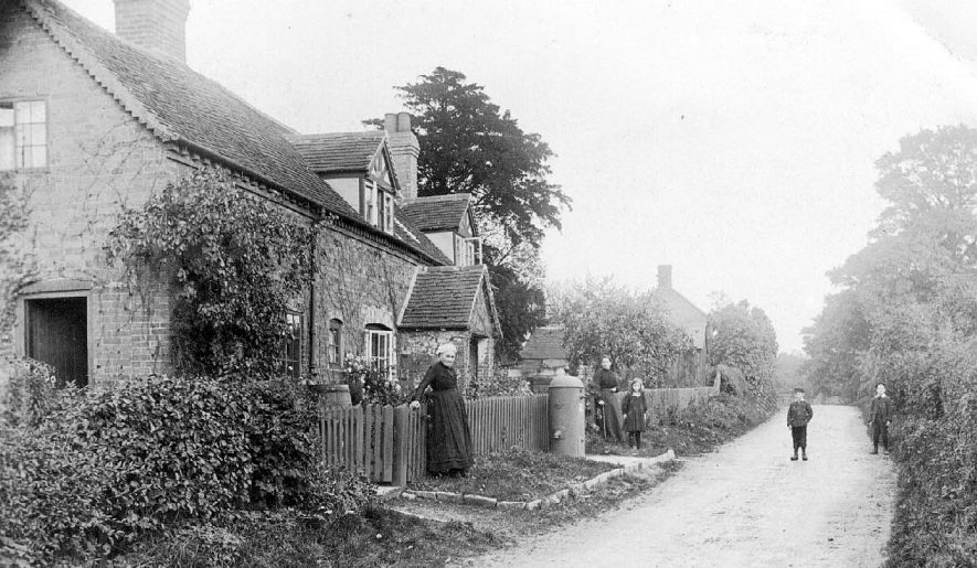 Snitterfield Road, Bearley, with unusual water pump? on roadside. Children standing in road and cottages to left.  1900s    IMAGE LOCATION: (Warwickshire County Record Office)