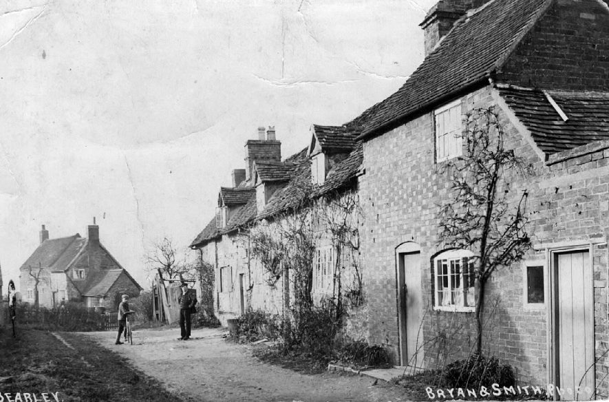 Bearley street with cottages, man in uniform and boy on bicycle.  1920s |  IMAGE LOCATION: (Warwickshire County Record Office)