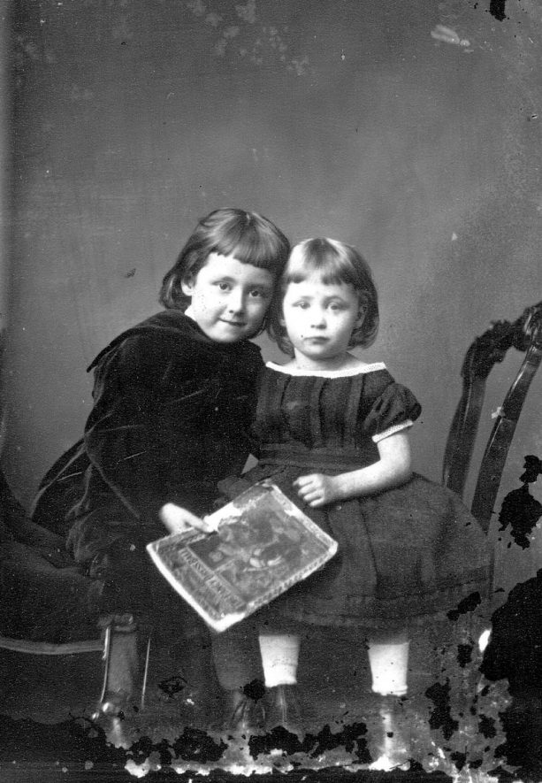 Portrait of two children with the surname Muntz. The child on the left is wearing a calliper on her right leg, possibly because of an old poliomyelitis.  1874 |  IMAGE LOCATION: (Warwickshire County Record Office) PEOPLE IN PHOTO: Muntz as a surname