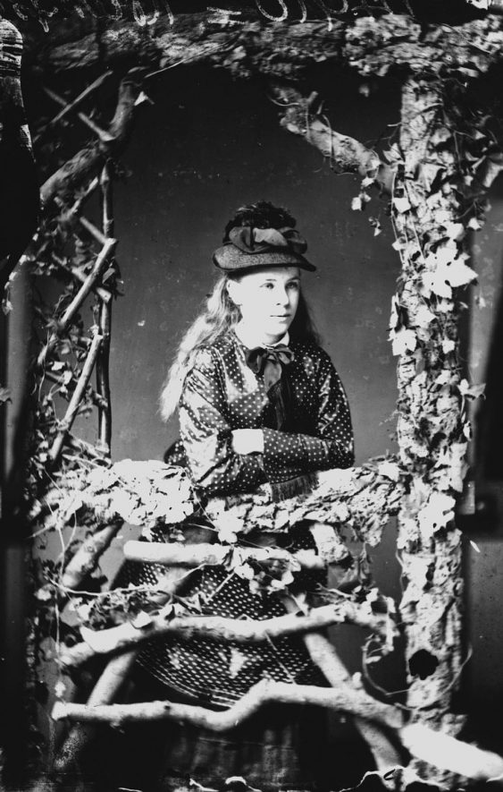 Portrait of a girl with the surname Hampton standing behind a rustic trellis photographers set.  1874 |  IMAGE LOCATION: (Warwickshire County Record Office) PEOPLE IN PHOTO: Hampton as a surname