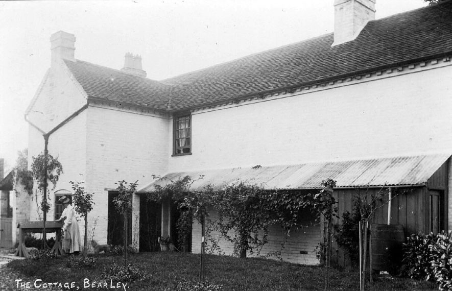 The Cottage, Bearley. Woman with bucket at wellside.  1900s |  IMAGE LOCATION: (Warwickshire County Record Office)