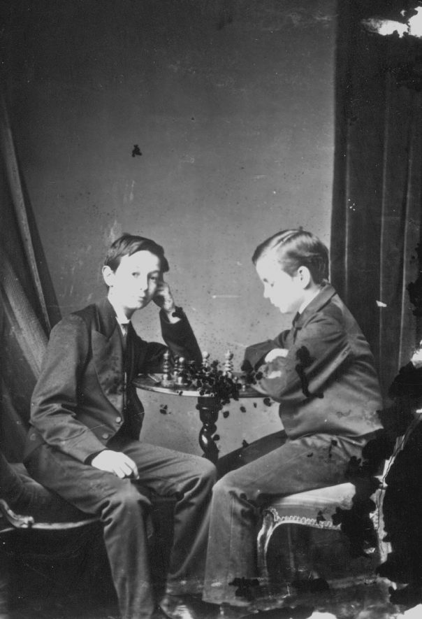 Portrait of two boys with the surname Kerby playing chess.  1874 |  IMAGE LOCATION: (Warwickshire County Record Office) PEOPLE IN PHOTO: Kerby as a surname