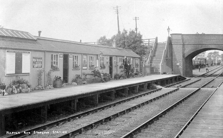 Napton and Stockton Railway Station, showing the station, platform, and railway bridge on the London and North Western Railway Line. Platform and station decorated with plants, rocks and advertisements; freight wagons seen behind the bridge. Men pictured on the platform and by the track, one in uniform of rail company.  1905 |  IMAGE LOCATION: (Warwickshire County Record Office)